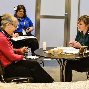 A nurse speaking to an elderly woman