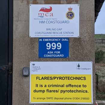 Signage saying dial 999 and ask for the Coastguard at a Coastguard rescue station