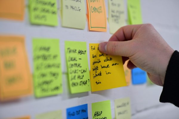 A person sticking a post-it note to a wall