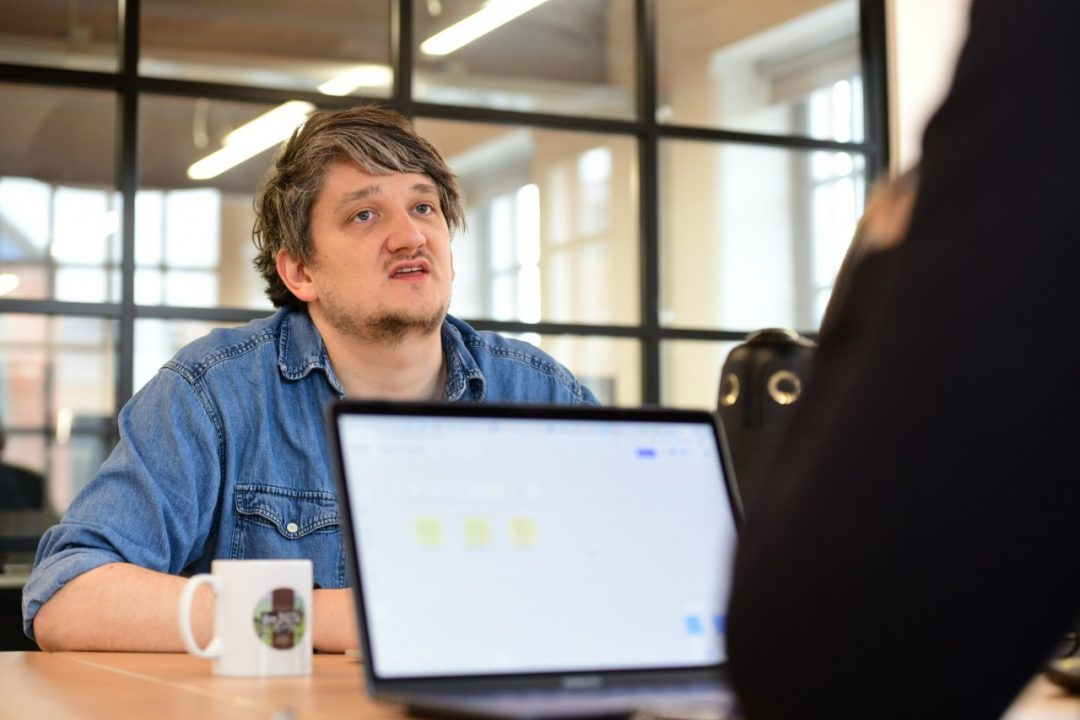 A person in a meeting talking to someone using a laptop