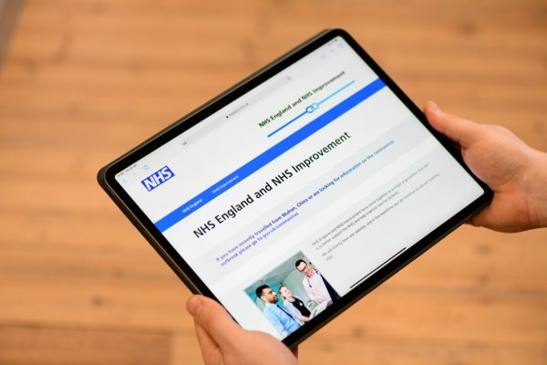 A person showing the NHS website on a tablet