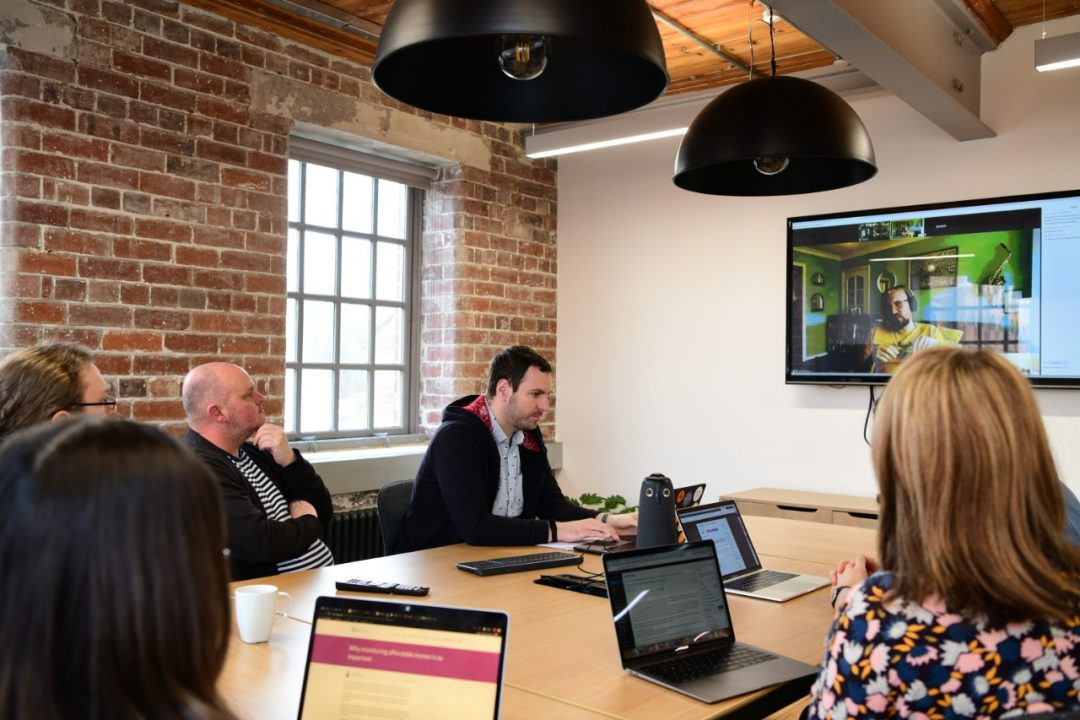 People in a meeting with a remote person on a screen