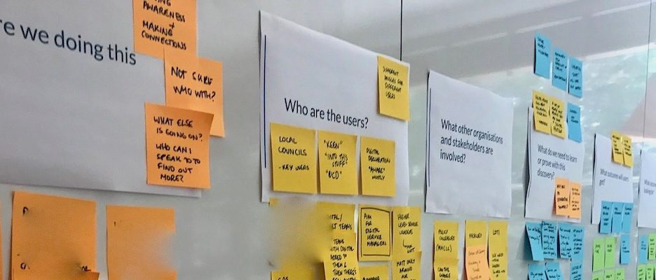 Photo of the questions and sticky notes answers on a wall.